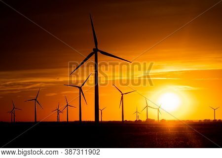 The Sun Sets On A Field Of Wind Turbines At A Wind Farm In Indiana, United States.