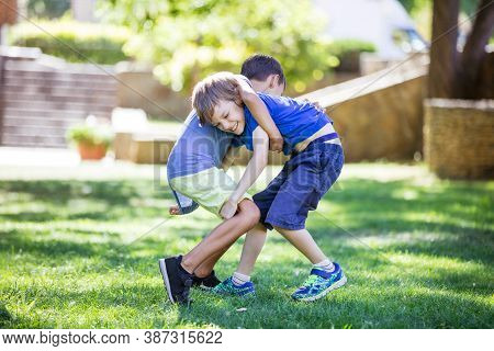 Two Boys Fighting Outdoors. Siblings Or Friends Wrestling In Summer Park. Siblings Rivalry.