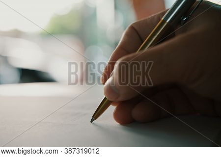 Businessman Holding Pen Writing On Paper For New Appointments Information In Organizer Concept, Male