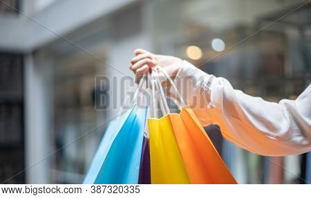 Young women carry colorful shopping and use their credit card to shop at the mall, Consumerism of As