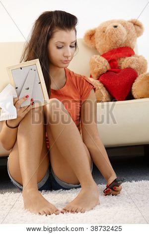 Lovelorn teenage girl sitting on floor at home, looking sad.