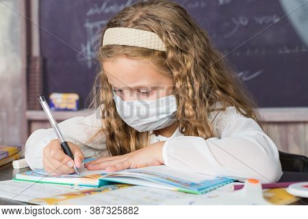 School Child With Protective Masks Against Coronavirus At Lesson In Class Room.girl Writing In Book.