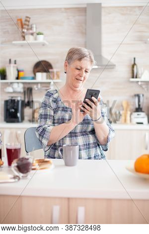 Elderly Woman Reading Message On Smartphone During Breakfast In Kitchen. Authentic Elderly Person Us