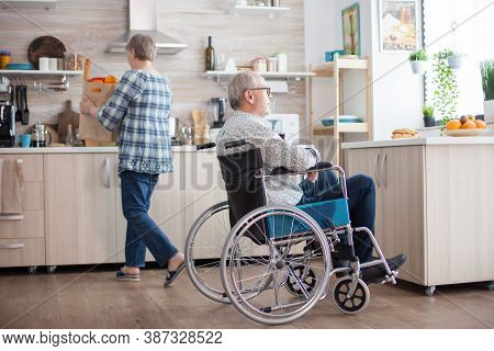 Invalid Senior Man Smiling Looking Through The Window In Kitchen And Wife Is Unpacking Groceries. In