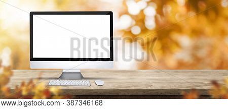 Autumn Background.blank Desktop Computer On Rustic Wood Table With Blur Forest Tree With Sunlight,au