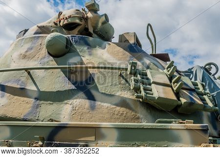 Gun Turret On Tank Displayed In Public Park Under Cloudy Sky.