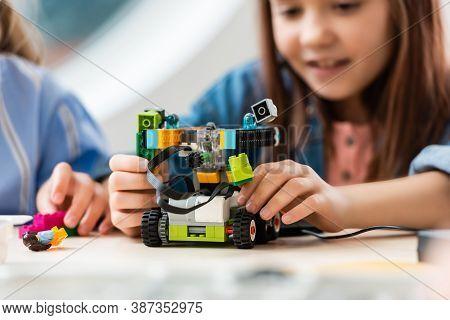 Selective Focus Of Schoolgirl Programing Robot Near Friend In Stem School, Background