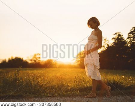 Young Pregnant Woman Holds Hands On Belly On Nature Background. Silhouette Of Pregnant Woman In Whit