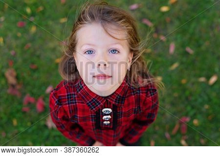 A Beautiful Girl With Blue Eyes Looks Up. Child In A Red Autumn Dress. View From Above. Camera From