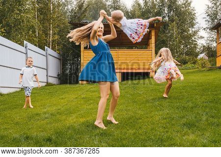Happy Kids And Mother Playing In Garden On Grass. Summer Time.