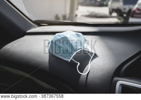 Medical Face Mask Placed On Console Inside To The Car , Coronavirus (covid-19) Prevention Concept