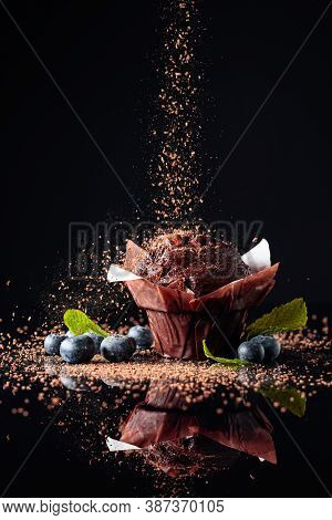 Chocolate Muffin Sprinkled With Chocolate Crumbs On A Black Reflective Background. Muffin With Berri
