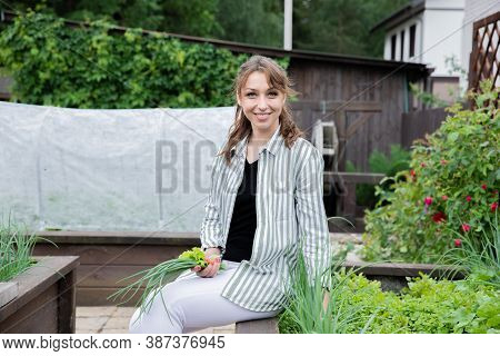 Attractive Happy Smiling Young Brunette Woman Posing With Onions And Lettuce In Her Hands In Kitchen
