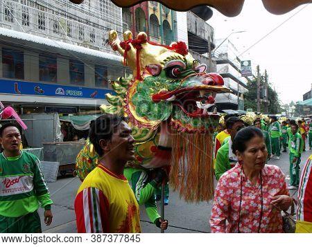 Bangkok, Thailand, November 14, 2015: A Group Of People Carrying A Dragon Stop At A Business At A Cl