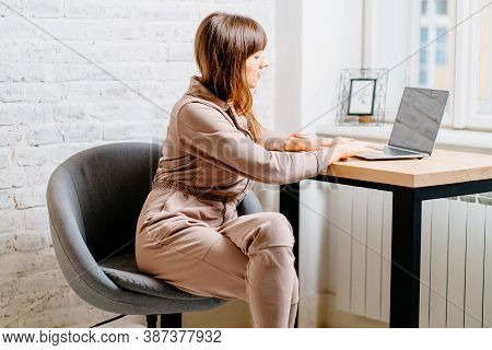 The Correct Position Posture When Working At The Computer. A Woman Sits At A Table With A Laptop Com