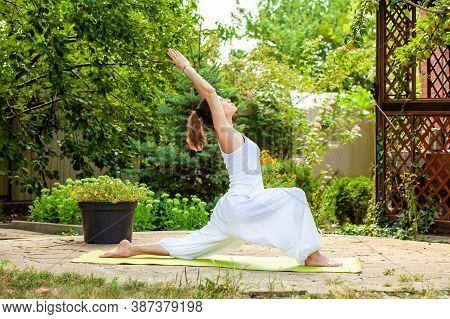 Young Woman Practices Yoga In The Summer Garden - Warrior Pose, Virabhadrasana I.