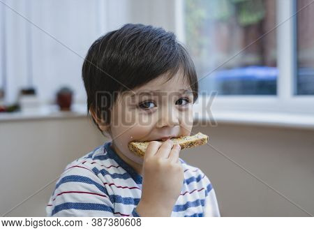 Close Up Face Preschool Boy Eating Honey On Toasted For His Breakfast Before Go To School, Cropped S