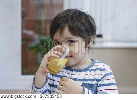 Indoor Portrait Cute Little Boy Drinking Home Made Orange Juice From Glass On After Finished Breakfa