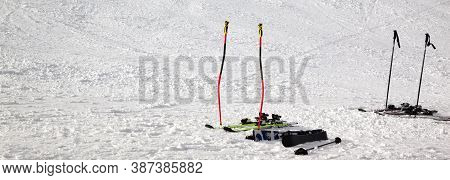 Skiing Equipment: Ski Poles, Skis On Snowy Sunlit Slope At Winter Day. Panoramic View.