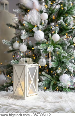 White Lantern On Fur Plaid, Against Background Of Burning Garlands Of Christmas Fir. New Year Or Chr