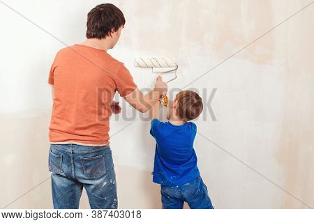 Young Family Painting House Wall. Father And Son Painting A Wall. Happy Family Renovating Their New