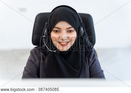 Arabian Or Muslim Woman Works In A Call Center Operator And Customer Service Agent Wearing Microphon