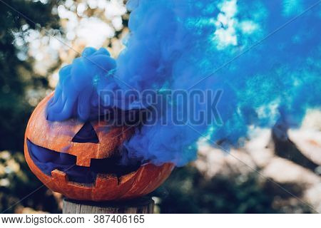 Spooky Carved Halloween Pumpkin With Blue Smoke Coming Out Of Holes In Autumnal Woods At Sunny Day.