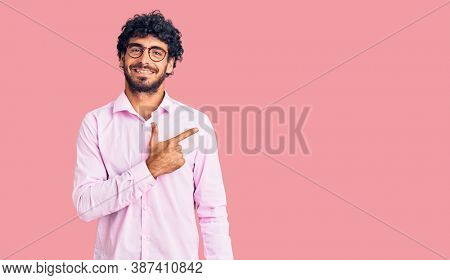 Handsome young man with curly hair and bear wearing business clothes cheerful with a smile of face pointing with hand and finger up to the side with happy and natural expression on face