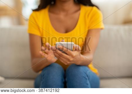 Closeup View Of Young Black Woman Using Mobile Phone For Work Or Studies On Sofa At Home. African Am