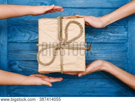 Woman With Children Holding A Gift In Hand On Wooden Background
