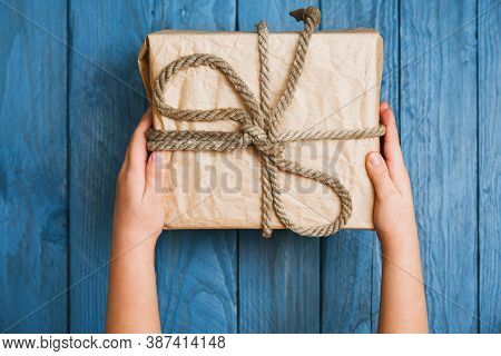 Hands Of A Child Holding A Gift, Top View Over Blue Wood Background