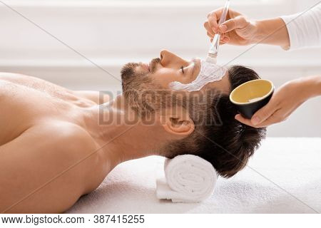 Side View Of Bearded Man Getting Face Treatment At Modern Spa Salon. Female Attendant Applying Nouri