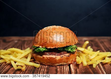 Delicious Fresh Crispy American Burger With Beef, Herbs, Onions And Potatoes On A Wooden Table