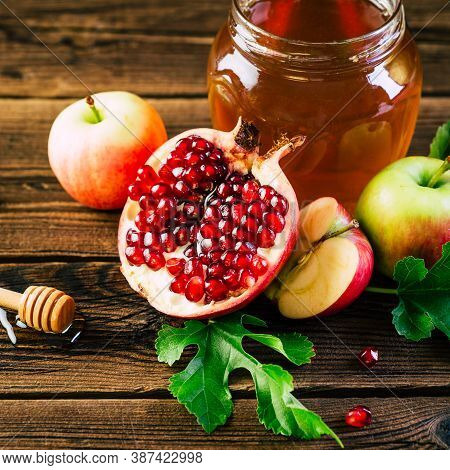 Rosh Hashana. Jewish New Year. Apples, Honey And Pomegranate On A Wooden Background.