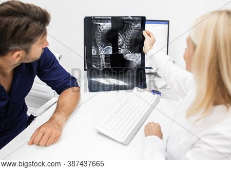 Neurologist Considers And Discusses With Man Patient An X-ray Image Of His Cervical Spine. Diagnosti