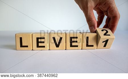 Time For Level 2. Hand Is Turning A Cube And Changes The Word 'level 1' To 'level 2'. Beautiful Whit