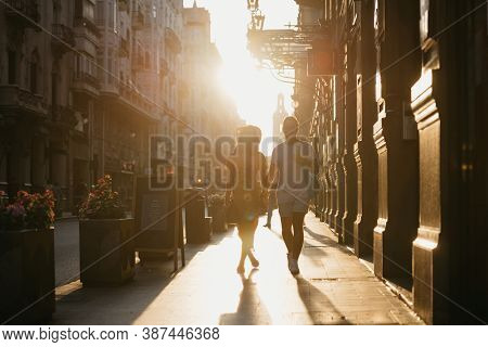 A Girl In A Hat And A Yellow Dress With A Plunging Neckline And Her Boyfriend With A Beard Are Walki