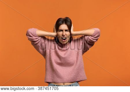 Hush. Portrait Of Beautiful Woman In Pink Sweater Covers Ears As Hears Very Loud Noise Or Music Squi