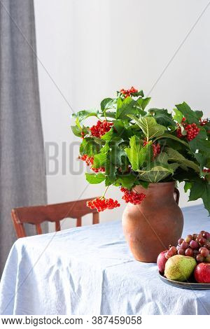 Home Interior, Table With Blue Tablecloth, Clay Vase With Viburnum And Fruits In A Plate