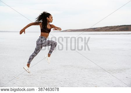 Image of athletic african american sportswoman running while working out on nature