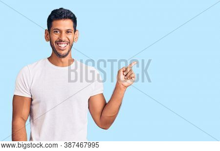 Young latin man wearing casual clothes with a big smile on face, pointing with hand finger to the side looking at the camera.