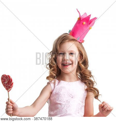 Beautiful little candy princess girl in crown with big pink heart lollipop