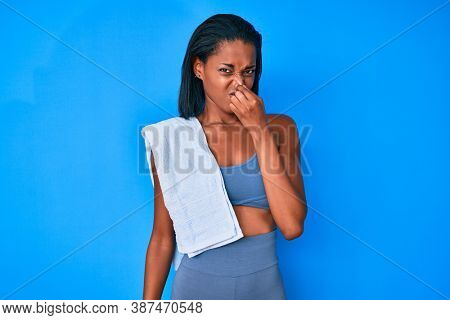 Young african american woman wearing sportswear smelling something stinky and disgusting, intolerable smell, holding breath with fingers on nose. bad smell