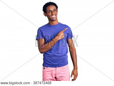 African handsome man wearing casual clothes and glasses cheerful with a smile of face pointing with hand and finger up to the side with happy and natural expression on face