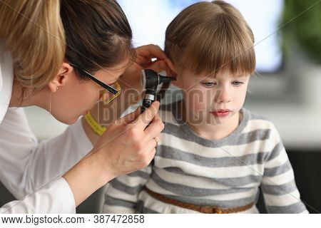 Woman Otorhinolaryngologist Examines Little Girls Ear With Otoscope In Clinic. Diagnostics And Treat