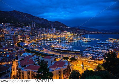 Aerial view of Monaco Monte Carlo harbour and illuminated city skyline in the evening blue hour twilight. Monaco Port night view with luxurious yachts