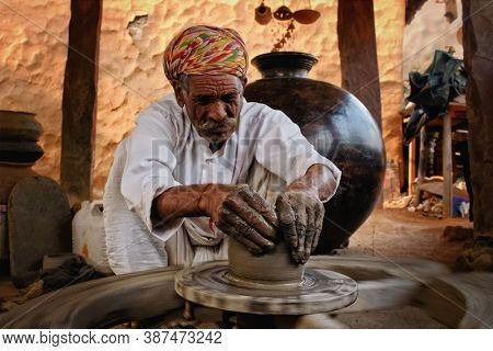 Indian potter at work: throwing the potter's wheel and shaping ceramic vessel and clay ware: pot, jar in pottery workshop. Experienced master. Handwork craft from Shilpagram, Udaipur, Rajasthan, India