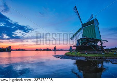 Netherlands rural scene - windmills at famous tourist site Zaanse Schans in Holland on sunset with dramatic sky. Zaandam, Netherlands
