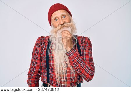 Old senior man with grey hair and long beard wearing hipster look with wool cap looking confident at the camera smiling with crossed arms and hand raised on chin. thinking positive.