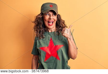 Middle age brunette woman wearing t-shirt and cap with red star symbol of communism pointing thumb up to the side smiling happy with open mouth